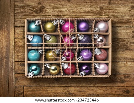 Colorful Christmas balls in cardboard box on old wooden backbround - stock photo