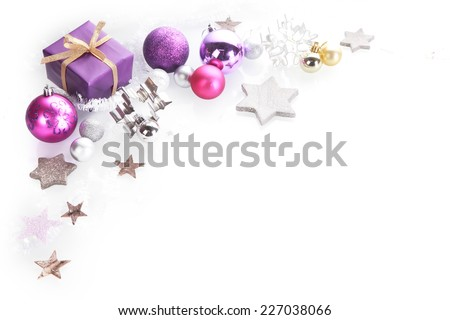 Colorful Christmas corner border background over white with copyspace with silver, pink and purple star decorations and gift - stock photo