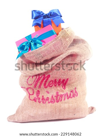 Colorful Christmas gifts in Santas rustic burlap sack with a Merry Christmas greeting on the side, over white - stock photo