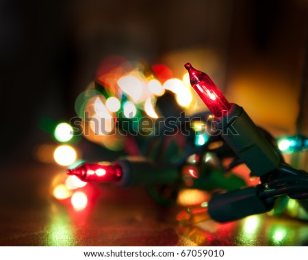 colorful christmas lights running along a mantelpiece, selective focus on single light