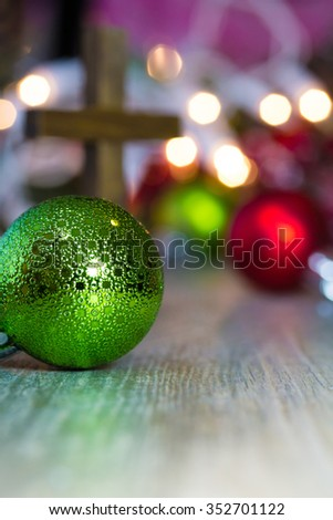 Colorful Christmas ornaments and lights on a wooden background with a christian cross.