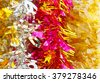 Colorful christmas tinsel texture and background with sunshine - stock photo