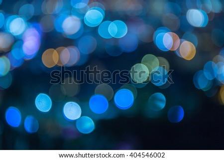 Colorful circle lights bokeh on dark background - stock photo