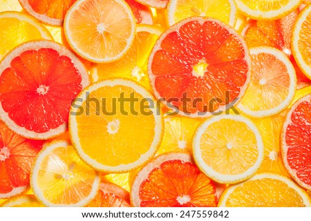 Colorful citrus fruit - lemon, orange, grapefruit - slices background. Backlit - stock photo