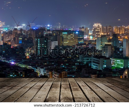 Colorful city night scene with modern skyscrapers, Taipei, Taiwan. Focus on wooden floor. - stock photo