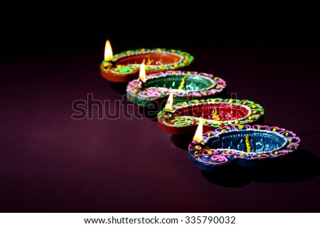 Colorful clay diya lamps lit during Diwali celebration  - stock photo