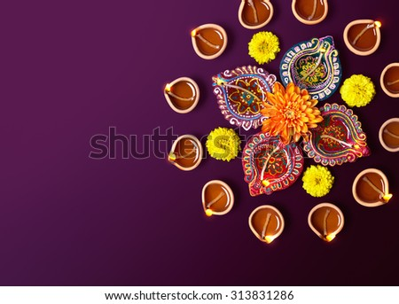 Colorful clay diya lamps with flowers on purple background - stock photo