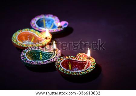 Colorful clay Diya (Lantern) lamps lit during Diwali celebration. Greetings Card Design Indian Hindu Light Festival called Diwali.  - stock photo