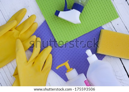 Colorful cleaning products on white wooden background - stock photo