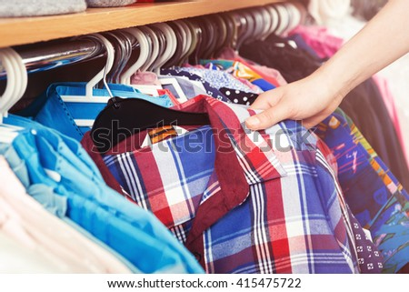 Colorful clothes hanging on a hanger and a female hand holding a shirt - stock photo