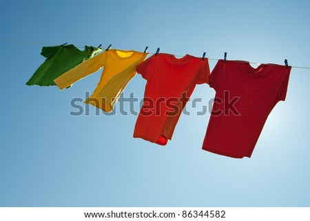 Colorful clothes hanging to dry in the blue sky, on a sunny and windy day. - stock photo