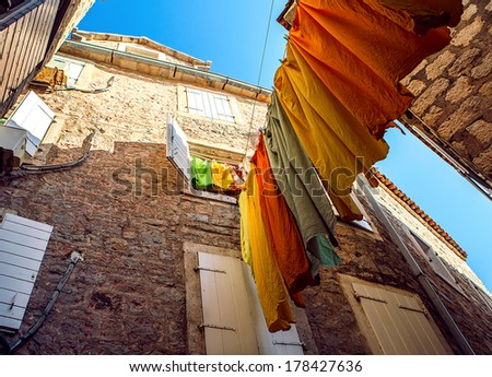 Colorful clothes hanging to dry on a laundry line on Budva street, Montenegro - stock photo