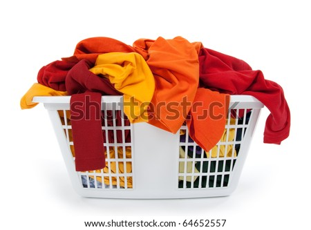 Colorful clothes in a laundry basket on white background. Red, orange, yellow. - stock photo