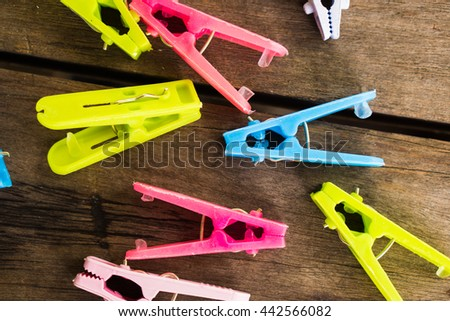 Colorful clothes peg,clothespin on wood background use for dry the clothes under the sun - stock photo
