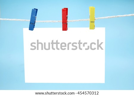 Colorful clothes pegs holding empty note against blue background