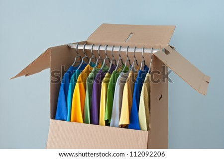 Colorful clothing hanging in a wardrobe box, ready for moving. - stock photo