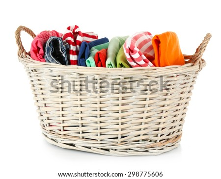 Colorful clothing in wicker basket isolated on white - stock photo