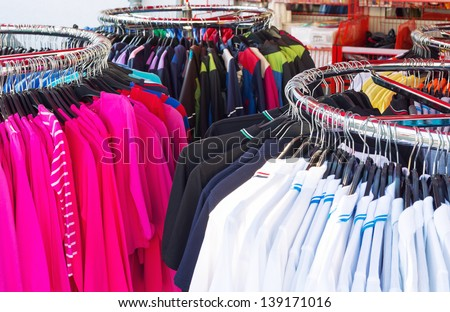 Colorful clothing on hangers in casual shop - stock photo