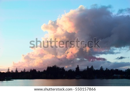 Colorful clouds rise up over a small mountain lake at sunset.