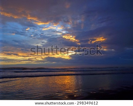 Colorful, Cloudy Sunset at the Ocean's Shore - stock photo