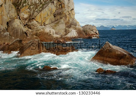 Colorful coastal waves crashing against a rocky shore with sea lions relaxing in the distance. - stock photo