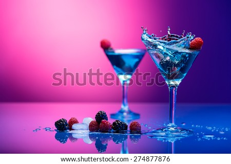 Colorful cocktails garnished with berries - stock photo