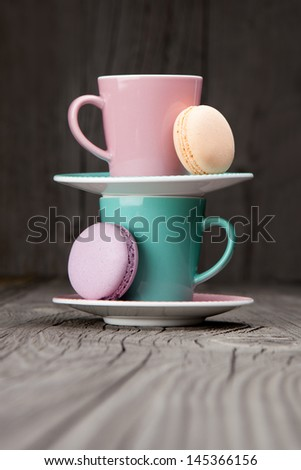 Colorful coffee cups and french macaroons on a dark wooden background - stock photo