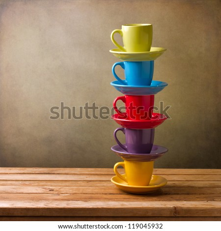 Colorful coffee cups on wooden table over grunge background - stock photo