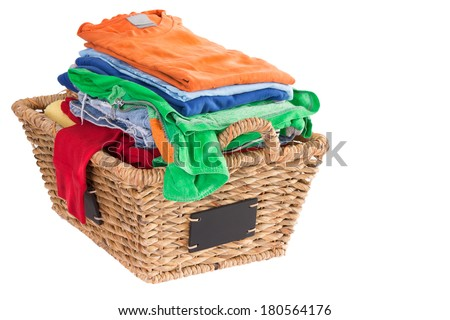 Colorful collection of clean washed fresh summer clothes in a rustic woven wicker laundry basket with blank attached labels, high angle view isolated on white with copy space to the right - stock photo