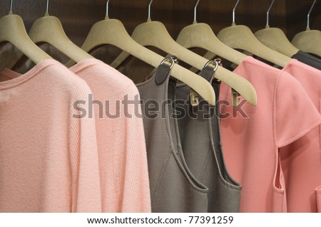 Colorful collection of women's clothes hanging on a rack - stock photo