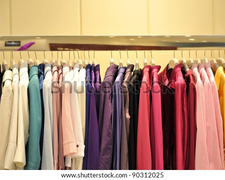Colorful collection of women's clothes hanging on a rack. - stock photo