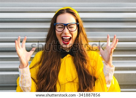Colorful comic funny emotional woman laughing posing and having fun outdoor. Pretty girl in yellow raincoat with fun glasses, long hair, red lips and black bow-tie. - stock photo