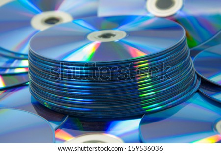 colorful compact discs set of DVD scattered on a table - stock photo