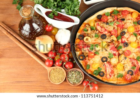 colorful composition of delicious pizza, vegetables and spices on wooden background close-up - stock photo