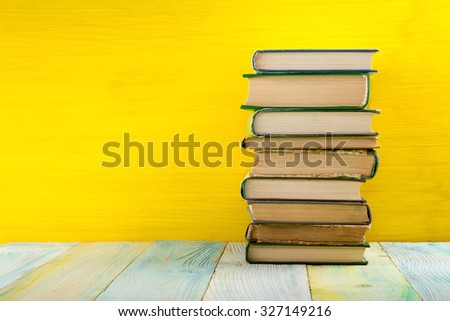 Colorful composition with vintage old hardback books, diary on wooden deck table and yellow background. Books stacking. Back to school. Copy Space. Education background - stock photo