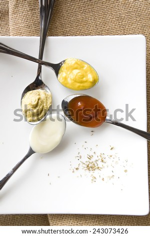 colorful condiments mayo mustard and tomato sauce on spoon - stock photo