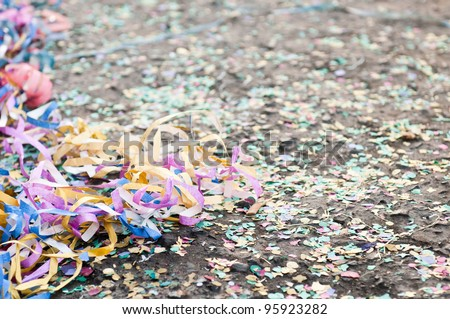 colorful confetti and streamers at the street after Carnival Parade (shallow DOF) - stock photo