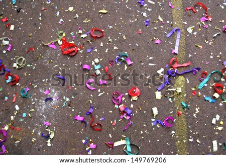 Colorful confetti in street after Chinese New Year parade  - stock photo