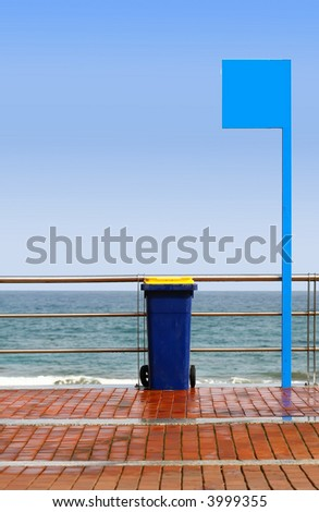 colorful containers for trash on the beach under blue sky - stock photo