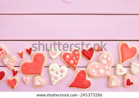 Colorful cookies with polka dots in heart-shape on pink wooden boards