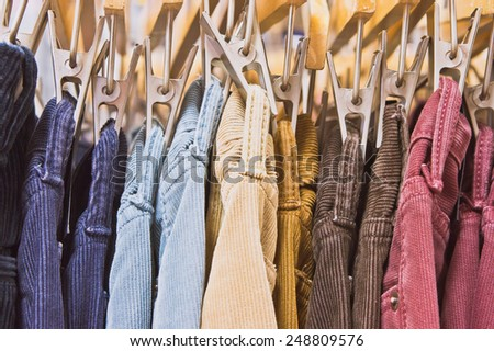 Colorful corduroy trousers in a store - stock photo