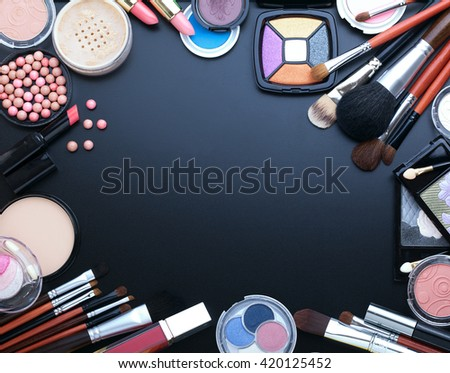 Colorful cosmetics on black wooden workplace with copy space. Cosmetics make up artist objects: lipstick, eye shadows, powder, tools for make-up.Top view selective focus.