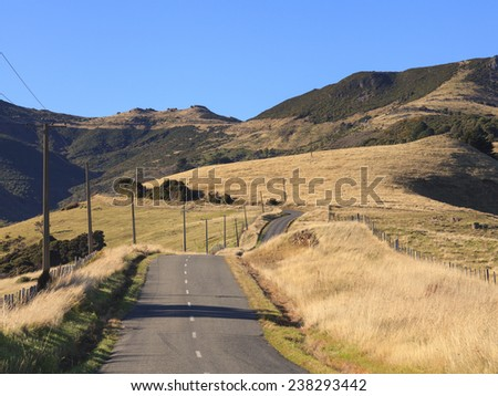Colorful countryside of tussock and mountains on the way to Akaroa, Canterbury region, South Island, New Zealand. - stock photo