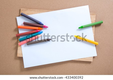 colorful crayons and blank paper - stock photo