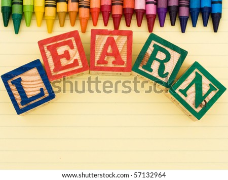 Colorful crayons on a sheet of lined paper,  Learning - stock photo