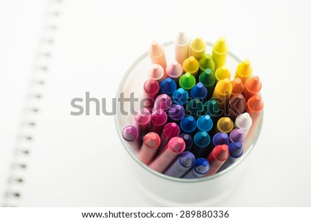 Colorful crayons placed on a new page of a white sketch book. Shallow depth of field for dreamy impressional feel . - stock photo