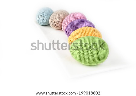 Colorful crocheted eggs on a white plate - stock photo