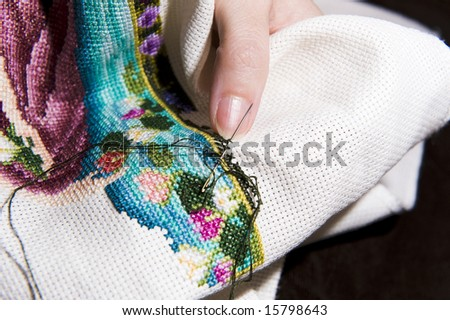 Colorful cross stitch art in the making, showing various color threads and a womans hands working with a needle. - stock photo