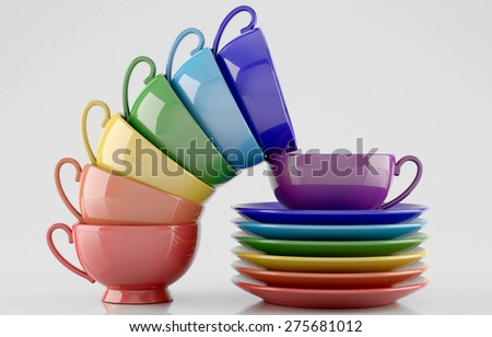 Colorful cups and saucers on white background - stock photo