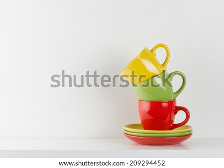 Colorful cups on white wooden shelf - stock photo